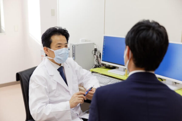 大腸癌患者さんに病状を説明している賀川義規医師